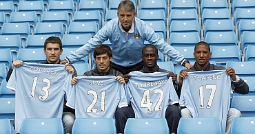 Manchester City's manager Mancini poses with new signings in Manchester