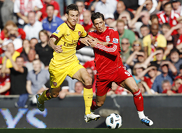 Liverpool's Fernando Torres (right) and Arsenal's Laurent Koscielny vie for possession