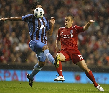 Liverpool's Joe Cole challenges Trabzonspor's Selcuk Inan during their Europa League playoff match
