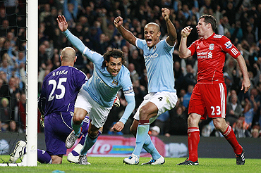 Manchester City's Carlos Tevez (2nd from left) celebrates after scoring against Liverpool on Mon