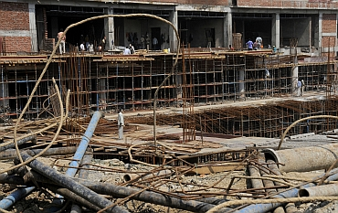 Labourers work at the construction site of the Shivaji stadium, which will be used as a training venue for hockey, during the 2010 Commonwealth Games