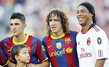 AC Milan's player Ronaldinho (right) with Barcelona's Carles Puyol (centre) and David Villa (left) before their friendly match at Camp Nou on Wednesday