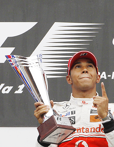 McLaren's Lewis Hamilton celebrates on the podium after winning the Belgian Grand Prix on Sunday