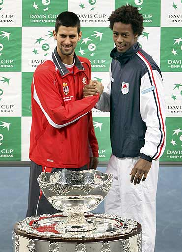 Serbia's Novak Djokovic (L) and France's Gael Monfils pose with the Davis Cup trophy