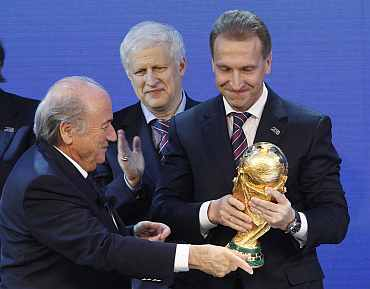 FIFA president Sepp Blatter hands over a copy of the World Cup to Russia's Deputy Prime Minister Igor Shuvalov