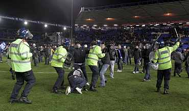 Birmingham City fans clash with the police on the pitch after team won their English League Cup soccer match against Aston Villa