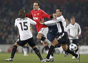 Valencia's Ricardo Costa and Angel Dealbert challenge Manchester United's Dimitar Berbatov during their Champions League Group C match in Manchester