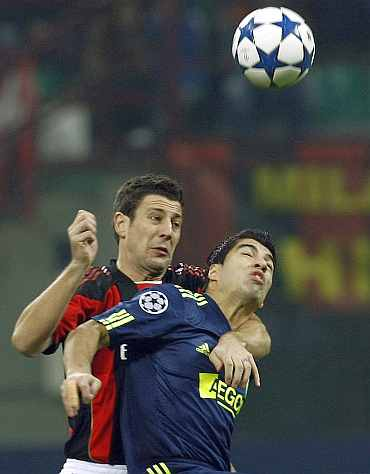 AC Milan's Bonera fights for the ball with Ajax's Suarez during their Champions League match in Milan