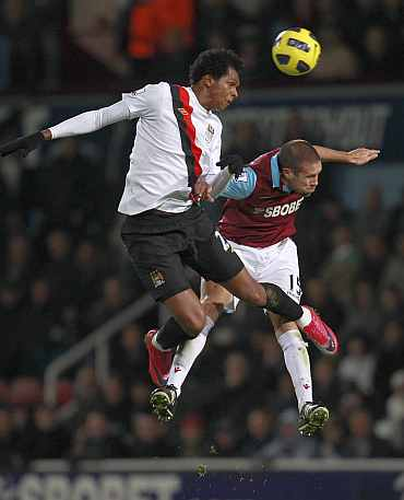 West Ham United's Matthew Upson challenges Manchester City's Jo during their EPL match