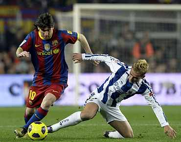 Barcelona's Lionel Messi fights for the ball against Real Sociedad's Griezmann during their match at Nou Camp Stadium
