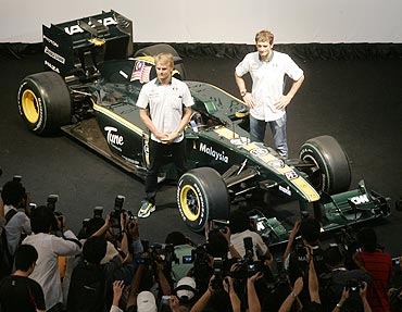 Lotus F1 F1 drivers Heikki Kovalainen of Finland (left) and Jarno Trulli of Italy pose with the Lotus Cosworth T127