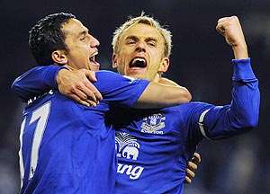 Everton's Tim Cahill (left) and Phil Neville celebrate after defeating Manchester City on Monday