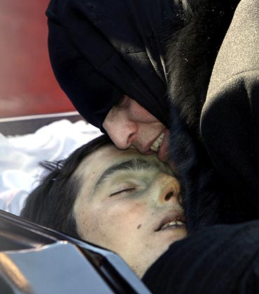 Dodo Kumaritashvili, the mother of Georgian luge competitor Nodar Kumaritashvili, embraces her son's body during a funeral in Bakuri