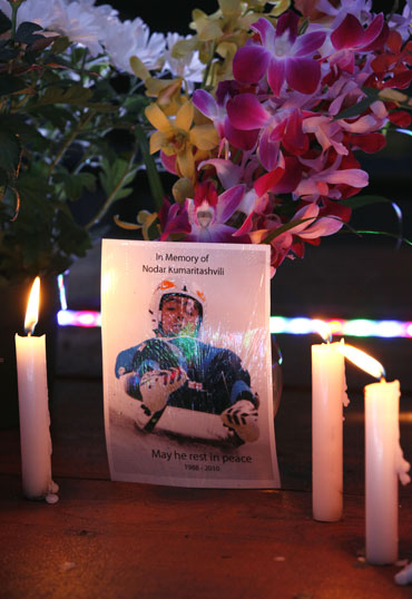 A postcard flanked by candles reads 'in memory of Nodar Kumaritashvili