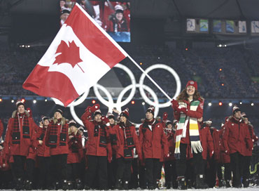 Flag bearer Hughes of Canada leads her country's delegation during the opening ceremony