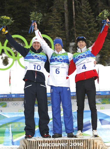 France's Vincent Jay (centre), Norway's Emil Hegle Svendsen (left) and Croatia's Jakov Fak celebrate during the flower ceremony after the men's 10 km sprint biathlon final
