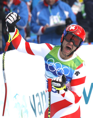 Switzerland's Didier Defago celebrates after crossing the finish line during the men's alpine skiing downhill event