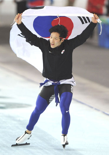 Mo Tae-bum of South Korea celebrates his victory in the men's 500 metres speed skating race