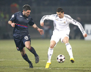 Real Madrid's Cristiano Ronaldo (right) challenges Olympique Lyon's Jeremy Toulalan