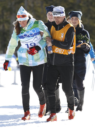 Slovenia's Majdic (left) is helped to the podium during the flower ceremony after the women's individual sprint classic cross-country final