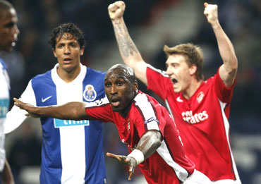 Arsenal's Sol Cambell (centre) and team-mate Nicklas Bendtner celebrate as Porto's Danii Alves (right) wears a dejected look