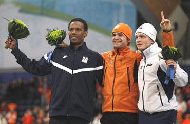 Gold medallist Tuitert of Netherlands (centre), silver medallist Davis of US (left) and bronze medallist Bokko of Norway, celebrate on podium during flower ceremony after men's 1500 metres speed skating race