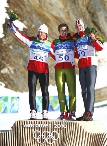 Ski jumpers Simon Ammann of Switzerland (centre) celebrates with Austria's Gregor Schlierenzauer (right) and Poland's Adam Malysz during the flower ceremony