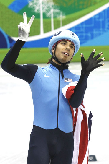 American speedskater and bronze medallist Apolo Anton Ohno holds up his fingers to indicate his seven Olympic medals