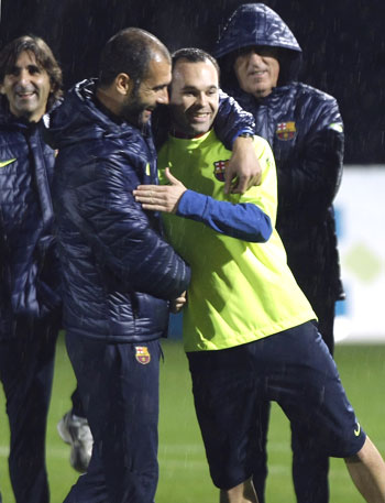 Barcelona's Iniesta (right) is embraced by coach Guardiola during a soccer training session