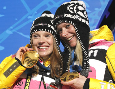 Evi Sachenbacher Stehle and Claudia Kuenzel of Germany pose with their medals during the medal ceremony