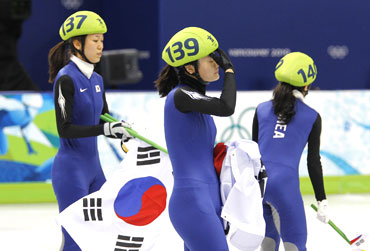 South Korea's Cho Ha-ri (left), Kim Min-jung (centre) and Lee Eun-byul react after their disqualification in the women's 3000 metres relay short track speed skating final