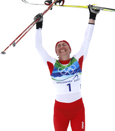 Poland's Justyna Kowalczyk celebrates after winning the women's 30 km mass start classic cross-country final