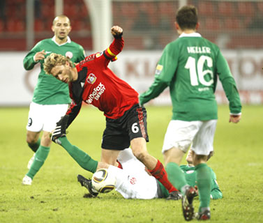 Bayer Leverkusen's Rolfes (in red)  is caught in a tangle as he vies for possession with Mainz' players