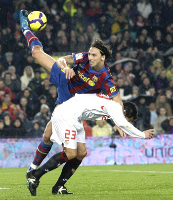 Barcelona's Zlatan Ibrahimovic (left) challenges Sevilla's Lolo