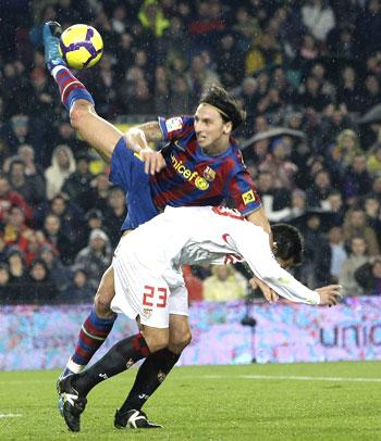 Barcelona's Zlatan Ibrahimovic (left) challenges Sevilla's Lolo