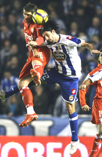 Deportivo Coruna's Juan Rodriguez (right) is involved in an aerial challenge with Sevilla's Ivica Dragutinovic on Wednesday