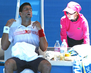 Novak Djokovic puts an ice pack around his neck as he takes a break during his match against Switzerland's Marco Chiudinelli