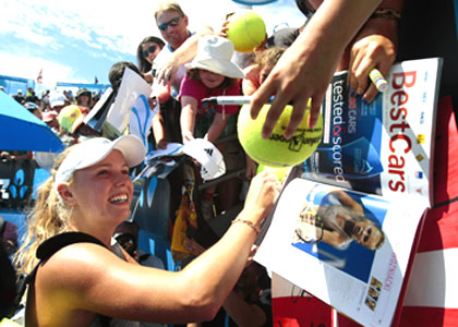 Denmark's Caroline Wozniacki signs autographs after defeating Julia Goerges of Germany