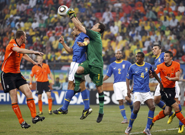 -Brazil's Felipe Melo (C) jumps with team mate goalkeeper Julio Cesar during their 2010 World Cup quarter-final soccer match against Netherlands