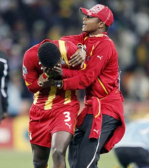 Asamoah Gyan is consoled by a team mate