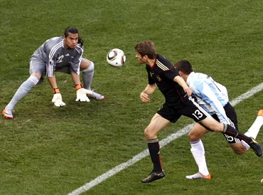 Germany's Thomas Mueller (centre) heads in the first goal past Argentina's goalkeeper Sergio Romero