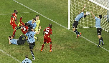 Uruguay's Luis  Suarez (right) saves the ball with his hands during a 2010  quarter-final against Ghana. He was consequently red-carded