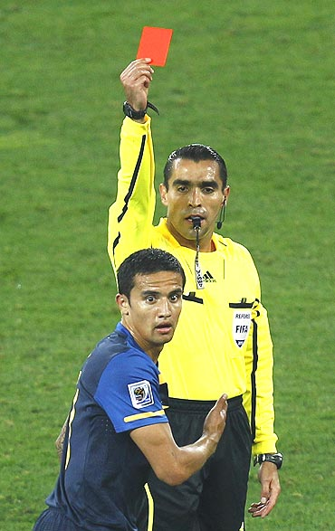 Referee Marco Rodriguez flashes the red card to Australia's Tim Cahill after his tackle on Germany's Bastian Schweinsteiger