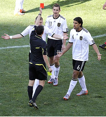 German players Bastian Schweinsteiger (left) and Sami Khedira (right) appeal to referee Alberto Undiano as he flashes the red card to Miroslav Klose (centre)