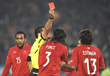 Mexican referee Marco Rodriguez shows the red card to Chile's Marco Estrada (13)