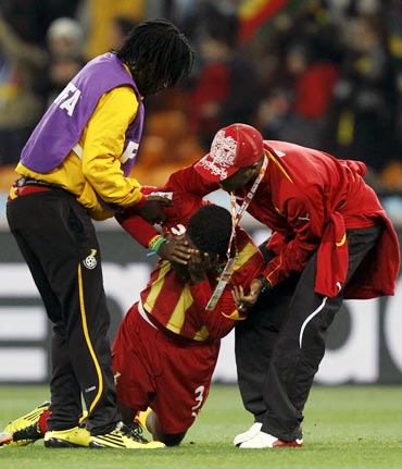 Ghana's Asamoah Gyan (centre) is consoled after the quarter-final match against Uruguay