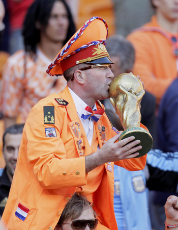 A Dutch fan kisses a replica of the World Cup trophy