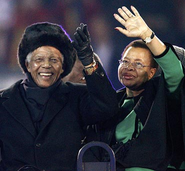 Mandela and his wife Graca Machel wave to the crowd at the Soccer City stadium in Johannesburg