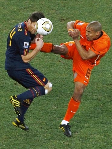 Spain's Xabi Alonso (left) gets a boot in his chest by Netherlands' Nigel de Jong