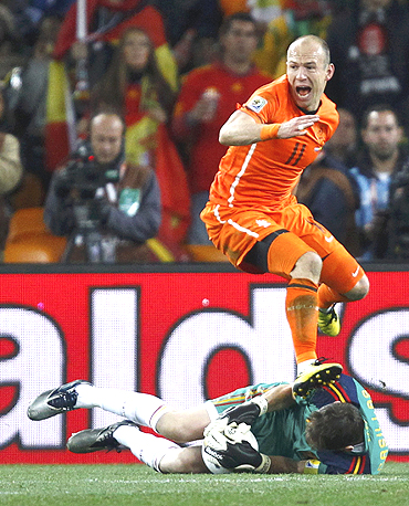 Netherlands' Arjen Robben looks back at referee Howard Webb as Spain's goalkeeper Iker Casillas dives to make a save